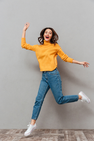 Foto de Full length image of Surprised happy brunette woman in sweater jumping and looking at the camera over gray background - Imagen libre de derechos