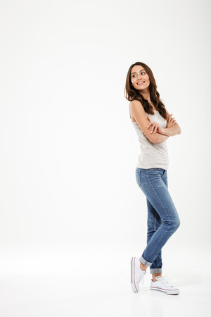 Photo pour Full length image of Pleased brunette woman posing sideways with crossed arms looking back over gray background - image libre de droit