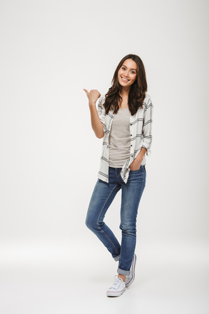 Photo pour Full length image of Smiling brunette woman in shirt pointing away and looking at the camera over gray background - image libre de droit