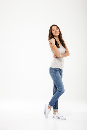 Foto de Full length image of Pleased brunette woman posing sideways with crossed arms and looking at the camera over gray background - Imagen libre de derechos