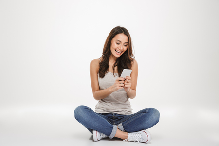 Photo pour Happy brunette woman sitting on the floor and writing message on smartphone over gray background - image libre de droit