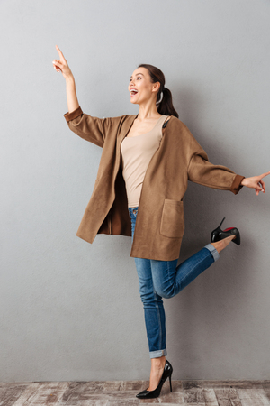 Foto per Full length of a cheerful young asian woman pointing finger away at copy space while standing and posing over gray background - Immagine Royalty Free