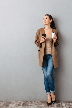 Photo pour Full length of a beautiful young asian woman holding mobile phone while standing and holding cup of coffee over gray background - image libre de droit