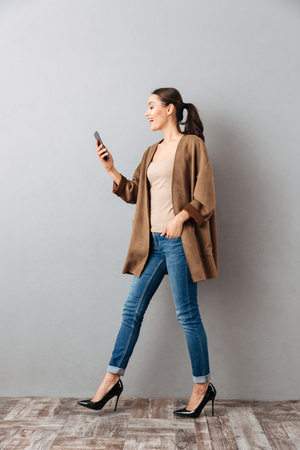 Photo pour Full length of a happy young asian woman using mobile phone while walking over gray background - image libre de droit