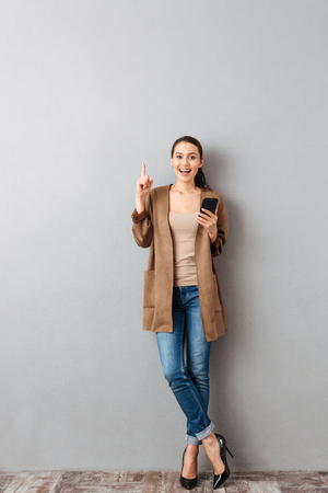 Photo pour Full length of a cheerful young asian woman pointing finger up while standing and holding mobile phone over gray background - image libre de droit