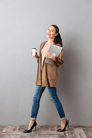 Photo pour Full length portrait of a smiling young asian woman holding cup of coffee and laptop computer while walking and looking at camera over gray background - image libre de droit
