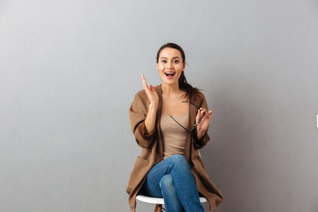Photo pour Portrait of a cheerful casual asian woman sitting on a chair and celebrating over gray background - image libre de droit