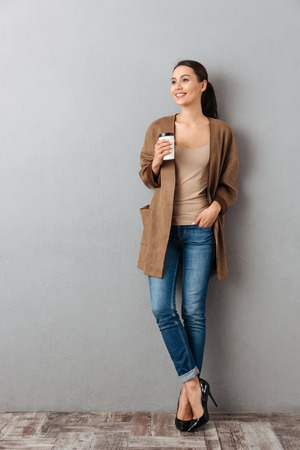 Foto de Full length of a smiling young asian woman standing and holding cup with coffee over gray background - Imagen libre de derechos