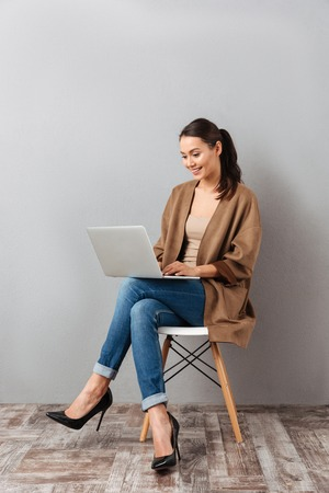 Photo pour Full length portrait of a happy casual asian woman holding laptop computer while sitting on a chair over gray background - image libre de droit