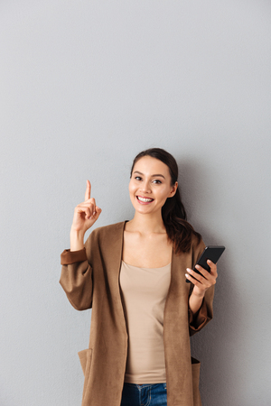 Foto de Portrait of a joyful young asian woman holding mobile phone while standing and pointing finger up at copy space over gray background - Imagen libre de derechos