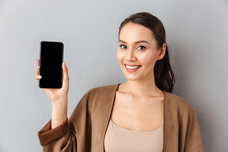 Foto de Close up of a smiling young asian woman showing blank screen mobile phone while standing and looking at camera over gray background - Imagen libre de derechos