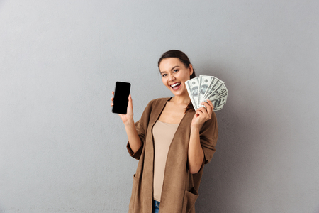 Foto de Portrait of a delighted young asian woman holding bunch of money banknotes and showing blank screen mobile phone over gray background - Imagen libre de derechos