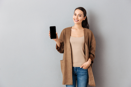 Foto de Portrait of a satisfied young asian woman showing blank screen mobile phone while standing and looking at camera over gray background - Imagen libre de derechos