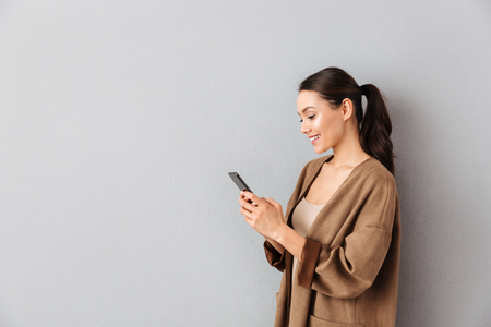 Photo for Portrait of an attractive young asian woman using mobile phone while standing with copy space over gray background - Royalty Free Image
