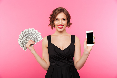 Foto de Portrait of a cheery girl dressed in black dress holding bunch of money banknotes and showing blank screen mobile phone isolated over pink background - Imagen libre de derechos