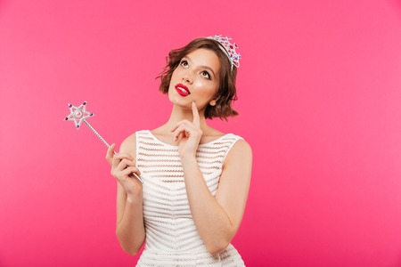Photo pour Portrait of a pensive girl wearing crown and holding magic wand while looking up isolated over pink background - image libre de droit