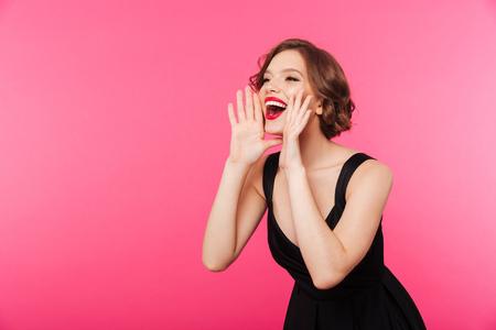 Foto de Portrait of a happy girl dressed in black dress shouting and looking away isolated over pink background - Imagen libre de derechos