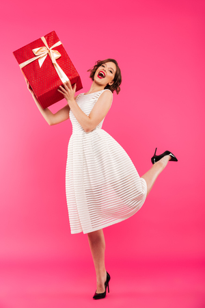 Photo pour Full length portrait of a joyful girl dressed in dress holding gift box while standing isolated over pink background - image libre de droit