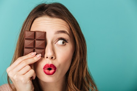 Photo pour Portrait of a cheery brown haired woman with bright makeup holding chocolate bar at her face isolated over blue background - image libre de droit