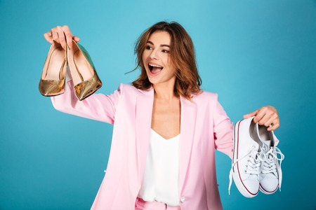 Photo pour Portrait of a happy woman dressed in pink suit holding pair of high heels shoes and pair of sneakers isolated over blue background - image libre de droit