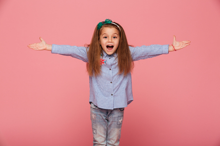 Photo pour Cheerful little girl in hair hoop posing with open hands against pink background, being friendly and welcoming - image libre de droit