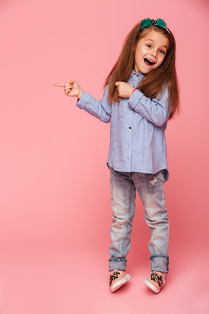 Photo pour Full-length picture of funny little girl gesturing pointing index finger isolated over pink background, copy space for your text or product - image libre de droit