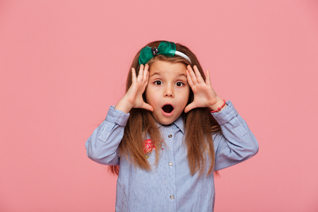Photo for Shot of female kid posing on camera with eyes and mouth wide open being emotional and surprised, over pink background - Royalty Free Image