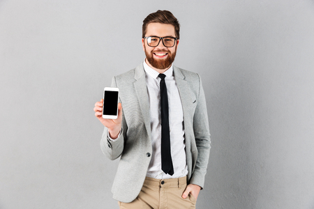 Photo pour Portrait of a confident businessman dressed in suit and eyeglasses showing blank screen mobile phone while standing and looking at camera isolated over gray background - image libre de droit