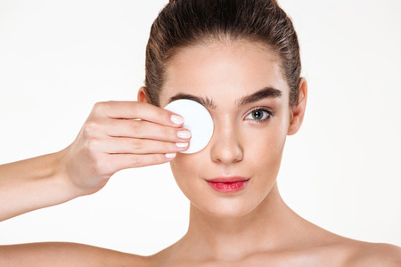 Foto de Close up photo of brunette beautiful woman removing her eye makeup with lotion and cotton pad, isolated over white background - Imagen libre de derechos