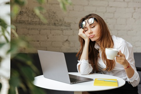 Photo for Portrait of a tired young businesswoman sitting at the table with laptop computer while holding cup of coffee and sleeping at a cafe - Royalty Free Image