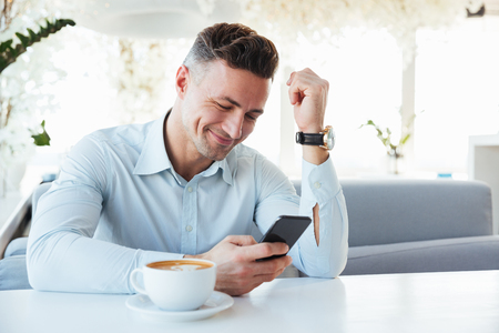 Photo for Image of happy elegant man sitting alone in city cafe with cup of cappuccino and typing text message using black mobile phone - Royalty Free Image