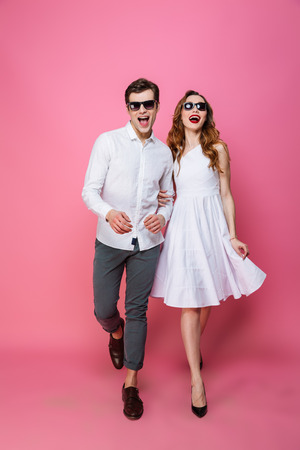 Photo pour Full-length photo of modern fascinating lady and guy trendy dressed walking together on camera olated over pink background - image libre de droit