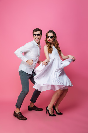 Photo pour Full-length portrait of young energetic man and woman in classy stylish clothing dancing on camera isolated over pink background - image libre de droit