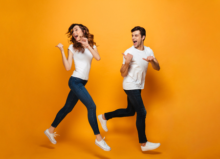 Photo pour Photo of energetic beautiful couple running together along yellow backgroundand, and pointing fingers backward on copyspace - image libre de droit