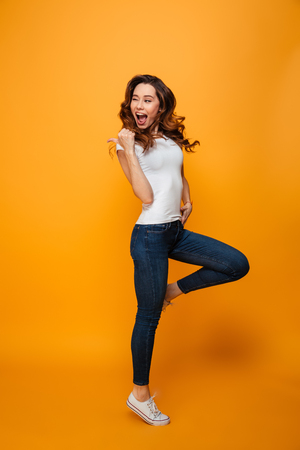 Photo for Full length image of Joyful brunette woman in t-shirt jumping and winks while looking and pointing away with thumb over yellow background - Royalty Free Image