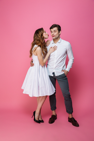 Photo pour Full length portrait of a young smartly dressed couple posing while standing together isolated over pink background - image libre de droit