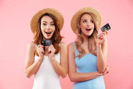 Photo pour Portrait of a two satisfied girls dressed in swimsuits and summer hats holding credit cards isolated over pink background - image libre de droit