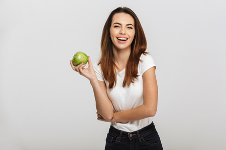 Photo for Portrait of a happy young woman holding green apple isolated over white background - Royalty Free Image