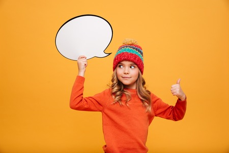 Photo pour Surprised smiling Young girl in sweater and hat holding blank speech bubble and showing thumb up while looking away over orange background - image libre de droit