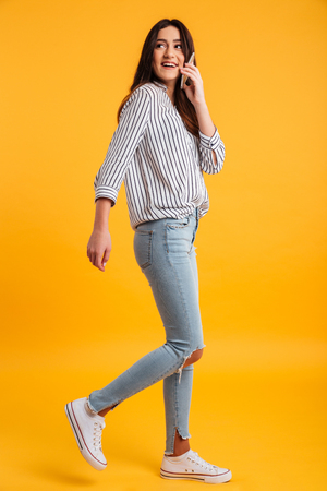 Photo pour Full length image of happy brunette woman in shirt walking while talking by smartphone and looking away over yellow background - image libre de droit
