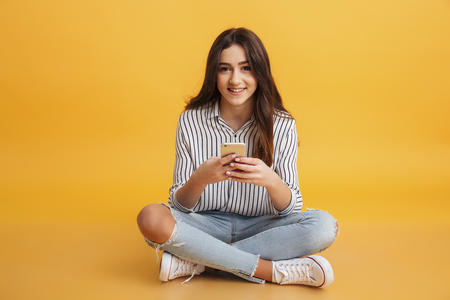 Photo for Portrait of a smiling young girl holding mobile phone while sitting and looking at camera isolated over yellow background - Royalty Free Image