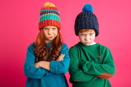 Foto de Photo of two displeased angry little children isolated over pink background wearing warm hats. Looking camera. - Imagen libre de derechos