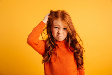 Photo pour Photo of confused little redhead girl with freckles standing isolated over yellow background. Looking camera. - image libre de droit