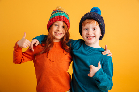 Photo pour Image of two funny little children standing isolated over yellow background wearing warm hats. Looking camera showing thumbs up. - image libre de droit