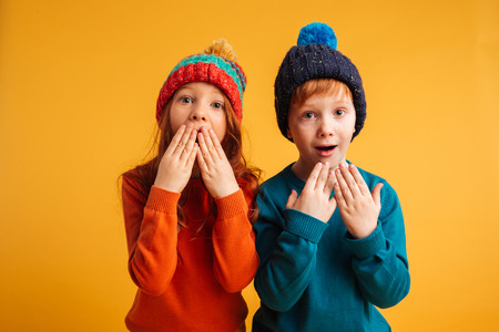 Photo pour Photo of two shocked surprised little children isolated over yellow background wearing warm hats. Looking camera with mouth opened. - image libre de droit