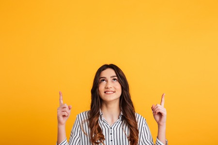 Photo pour Picture of Smiling brunette woman in shirt pointing and looking up over yellow background - image libre de droit