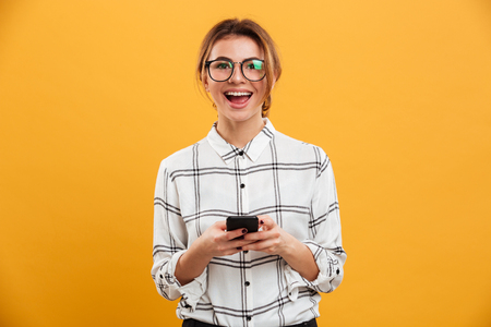 Photo pour Portrait of beautiful woman in plaid shirt and eyeglasses posing on camera with mobile phone in hands isolated over yellow background - image libre de droit