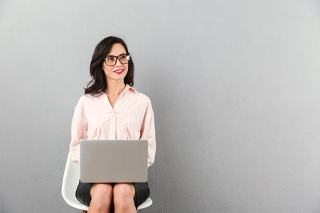 Photo pour Portrait of a smiling businesswoman in eyeglasses looking away at copy space while sitting in a chair and using laptop computer isolated over gray background - image libre de droit