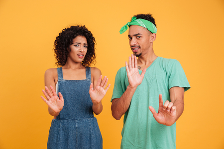 Photo pour Portrait of a disgusted young african couple dressed in summer clothes gesturing with hands isolated over yellow background - image libre de droit