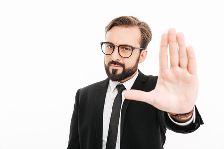Photo pour Image of serious businessman standing isolated over white background showing stop gesture. - image libre de droit
